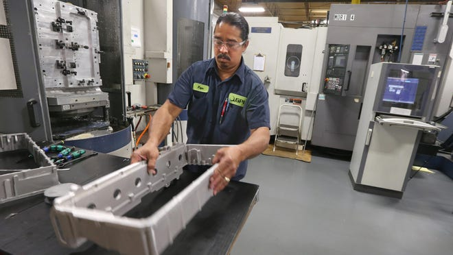 Luis Velazquez loads parts Thursday into a Moriseike SH5000 Flexible Machining Center at Global Precision Industries in Chili. The advanced milling machine is one of two at GPI.