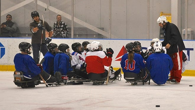 Coach Joe Wedge (r) talks to members of the Rangers sled hockey team and a couple of clinic participants. Photo from Jan 19, 2017.