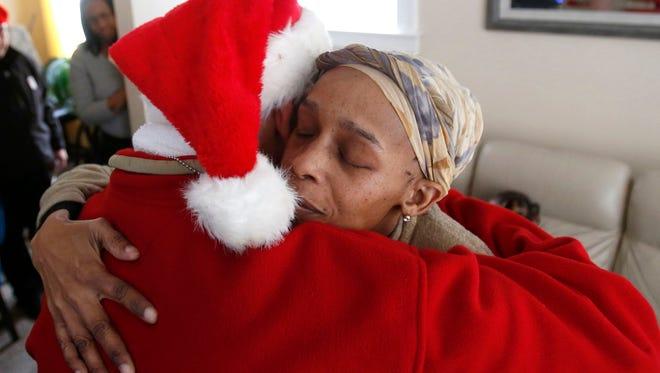 Sabrina Boyd of Lincoln Park gives a long hug to Secret Santa Elf 32A after receiving $400 onFri., Dec. 15, 2017.