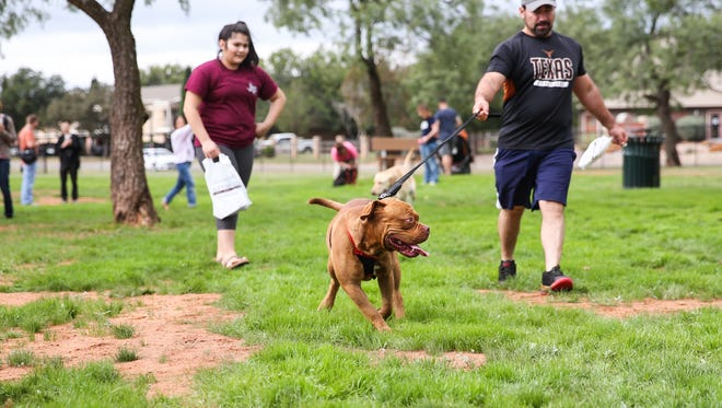 Luis Suarez walks with his dog through the park during the grand opening of the dog park Saturday, Oct. 21, 2017, along the Red Arroyo Trail.