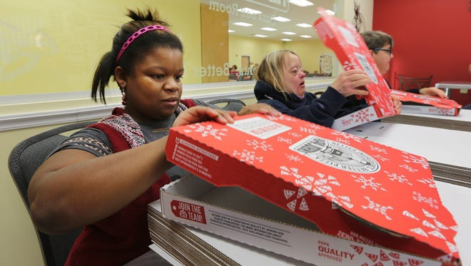 Jennifer Avery, left,  and  Cindy Kolarik, right, are part of a team of participants at St. Mary's Center who fold boxes every week for a Papa John's location in Middletown.  The group gets pizza twice a week for folding about 300 boxes.