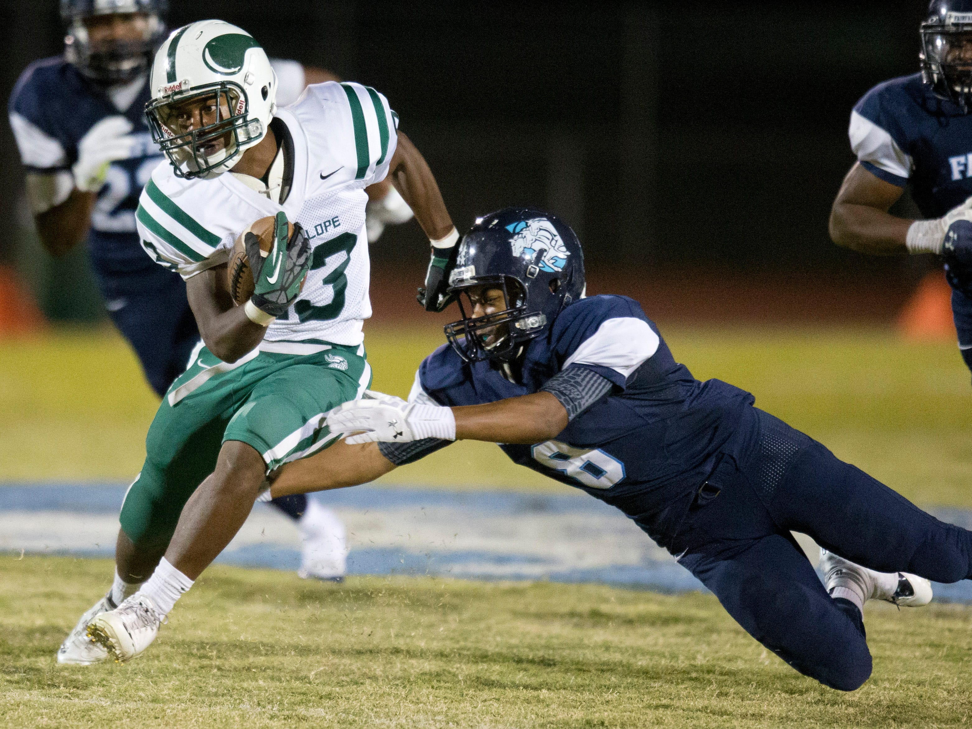 PNI0928-spt betty fairfax 0925130313tlb -- Phoenix Sunnyslope's Tim Fryson gets past Betty Fairfax's Deric Cameron during Friday's football game in Laveen. Pat Shannahan/The Arizona Republic