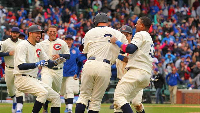 Cubs catcher David Ross gets mobbed after his game-winning hit in the 11th inning against the Kansas City Royals at Wrigley Field.