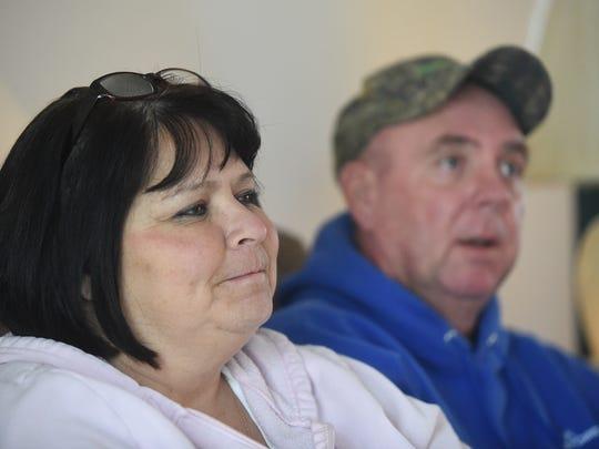 Karen Jones, left, of Gassville, listens as her husband,