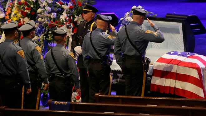 Law enforcement officers line up to salute Dallas Police Sr. Cpl. Lorne Ahrens before his funeral service at Prestonwood Baptist Church in Plano, Texas, on July 13, 2016.