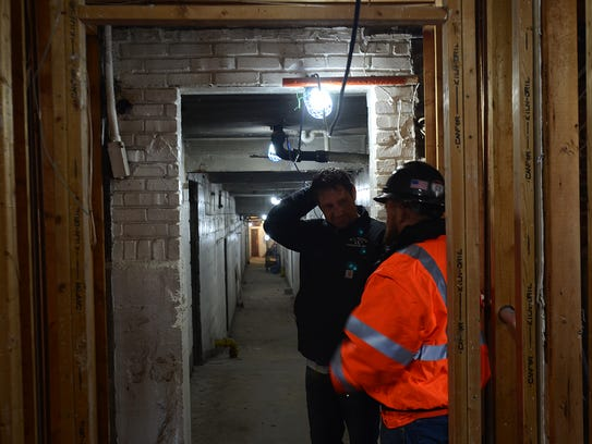 Workers walk through the St. Clair Inn to survey the