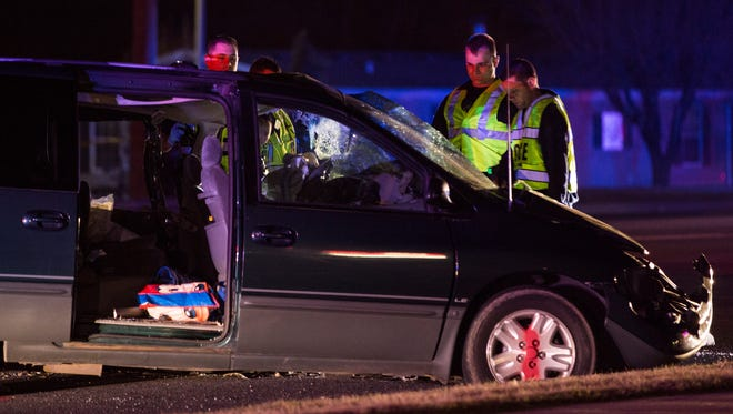 Lawrence Police Department officers look over a van involved in a serious wreck Tuesday night near 52nd Street and Pendleton Pike.