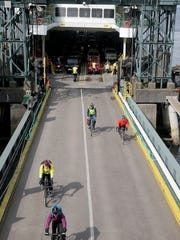 Bicycle commuters depart from the Bainbridge Island ferry at Colman Dock in Seattle on Monday.
