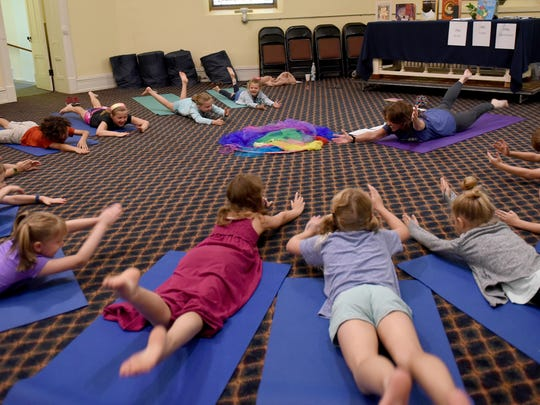 Yoga teacher Karen Scott leads kids in a yoga session during Peace Village Camp at United Church of Granville. Scott teaches youth yoga at Breathe @ Granville Yoga.