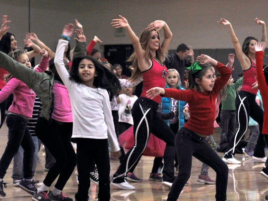 """Members of the Dallas Cowboys Cheerleaders dance with children during """"Cheer to Fitness"""" at the Dyess Air Force Base Fitness Center Friday."""