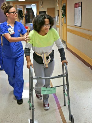 After therapy, Occupational Therapist Molly Duncan, left, walks Monique'ka Lee to her next therapy location at Riley Hospital for Children, Wednesday, December 23, 2015.  The Arlington High School volleyball player was hit by a car after getting off a city bus on December 1, 2015.  She has a variety of therapies daily, including occupational, physical, and speech, as well as being assessed for school.  She continues to improve every day.