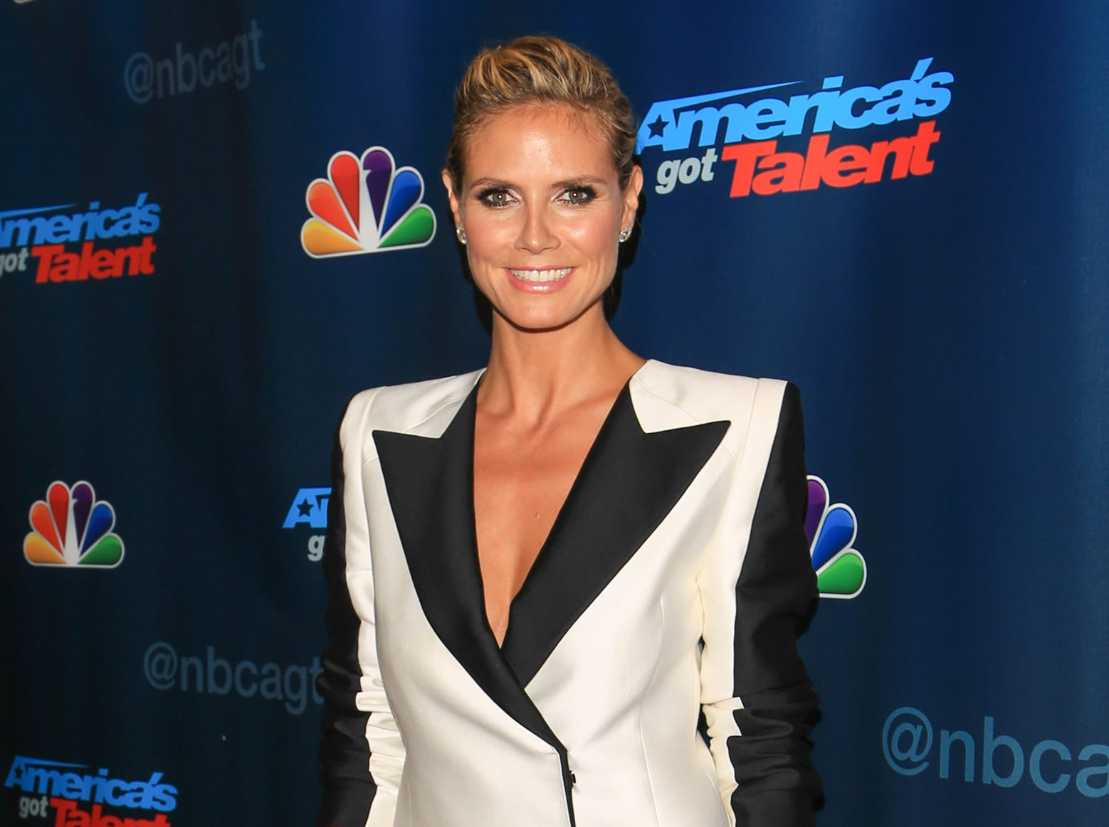 Heidi Klum cuts a stirking figure in a black and white Thomas Wylde tuxedo jacket, The Row trousers and Saint Laurent heels for her appearance on the 'America's Got Talent' Season 8 red carpet on Aug. 7 in New York.