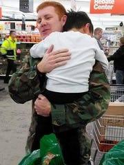 Yandel Sanchez hugs airman Shawn Provot following his shopping excursion at Fleet Farm.