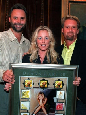 """A 1996 picture of a celebration for Deana Carter's successful debut album, """"Did I Shave My Legs for This?"""" Left to right, former Capitol Records chief Scott Hendricks, Deana Carter and co-producer Chris Farren"""