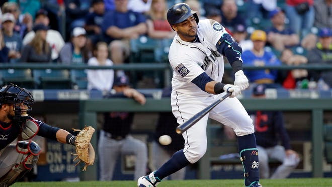 Seattle Mariners' Nelson Cruz (right) checks his swing as he strikes out looking to end Saturday's game against Cleveland.