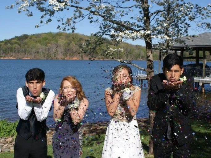 From left, Carlos Quintanilla, Victoria Noles, Kelly Hunt and Leo Barahona blow confetti in one of their prom pictures. They attended Lenoir City High School's prom.