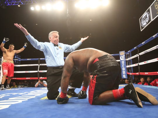 Referee Jack Russell stops the fight after Tommy Washington is unable to get up for a standing count after a combination from Taishan Dong, a 6-foot-11 boxer from China.