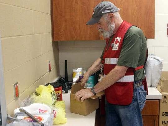 Red Cross Shelter Supervisor Scott Goldsmith opens a box with food and medical aid at the FEMA Dome after Hurricane Harvey displaced families Wednesday, Aug. 30, 2017, at Tulsa-Midway High School in Corpus Christi, Texas. Harvey struck the Texas Coastal Bend as a Category 4 Friday, August 25, 2017.
