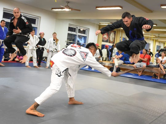 Robert Prieto leaps over instructor Elijah Reyes' belt at the Figo'/Bonsai Academy Guam in the International Sports Center in Anigua on Oct. 13