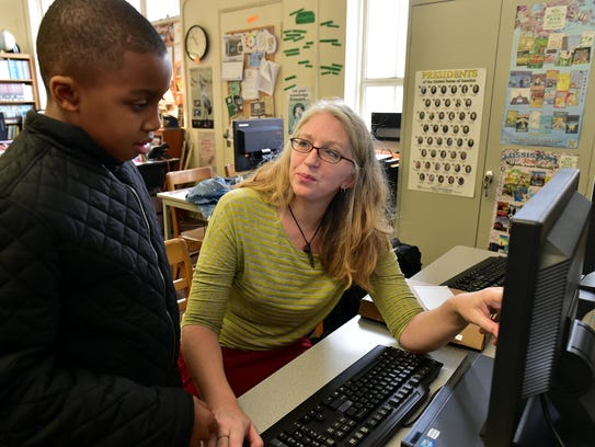Librarian Kacy Hellings talks to fourth-grader Collin