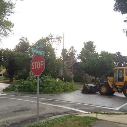 Crews clear downed tree branches from a street in Sturgeon
