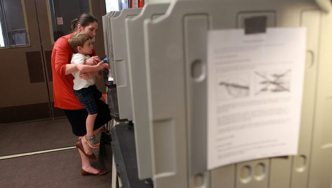 Michelle Croft gets help from her 3-year-old son, James Beard, as she votes at Lemme Elementary on Tuesday, Sept. 8, 2015.