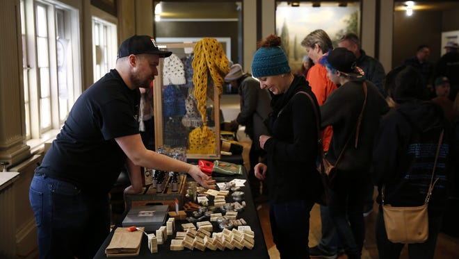 Aaron Naden, left, owner of Bearded Oregon, describes his products to Ashley Robinson of Salem during a pop-up event at Ike Box in Salem, Oregon, Saturday, Nov. 25, 2017.
