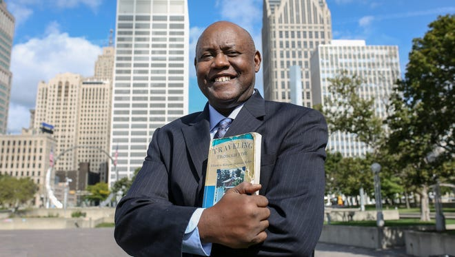 Cliff Russell, a local journalist and radio personality, has visited 1,200 of Michigan's 1,800 historical markers and is photographed at one of them, the Landing of Cadillac, in Hart Plaza in downtown Detroit on Thursday, Sept. 7, 2017. Russell read about this markers in Laura Ashley's book Traveling Through Time that he holds in his hands. Antoine de la Mothe Cadillac landed near the present intersection of West Jefferson and Shelby and planted the flag of France taking possession of the territory in the name of King Louis XIV.