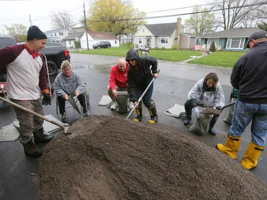 Neighbors along Edgemere Drive in Greece, fill sand bags to fight back the rising waters of Lake Ontario. From left are Jim Peer, Rene Hiebler, Kevin Francis, Kathy Allen, Heidi Peer and Chris Mazzaferro.
