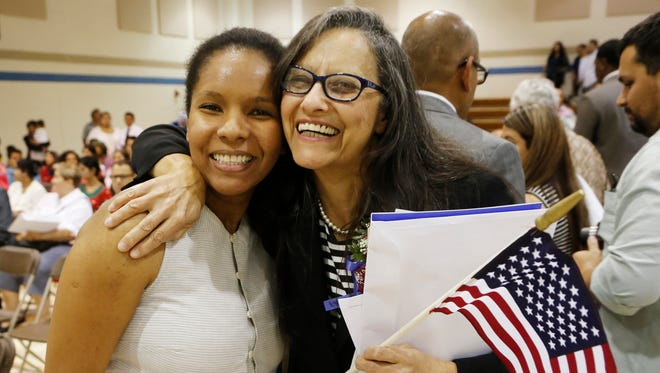 Daleth Assad, right, embraces Thalita Mendes following Naturalization Ceremonies Friday, September 16, 2016, at the former Burtsfield Elementary School in West Lafayette. Assad, who is originally from Brazil, was sworn in as a naturalized American citizen.