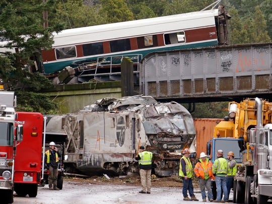 Cars from an Amtrak train lay spilled onto Interstate 5 below as some train cars remain on the tracks above Monday, Dec. 18, 2017, in DuPont, Wash.