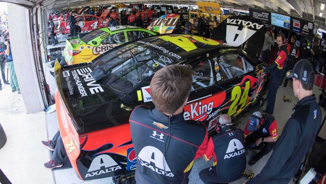 Teams for Kevin Harvick (4), Kyle Busch (18) and Jeff Gordon (24) work in the Sprint Cup garage at Texas Motor Speedway.