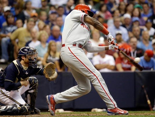 Philadelphia Phillies' Domonic Brown hits a two-run single during the fifth inning of a baseball game against the Milwaukee Brewers Tuesday, July 8, 2014, in Milwaukee. (AP Photo/Morry Gash)