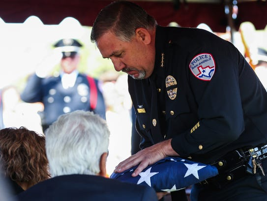 San Angelo Police Chief Frank Carter hands a flag to