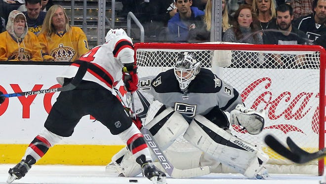 New Jersey Devils center Adam Henrique (14) squares off against Los Angeles Kings goalie Peter Budaj (31) in the second period of an NHL hockey game in Los Angeles Saturday, Nov. 19, 2016. The Kings won, 4-2. (AP Photo/Reed Saxon)