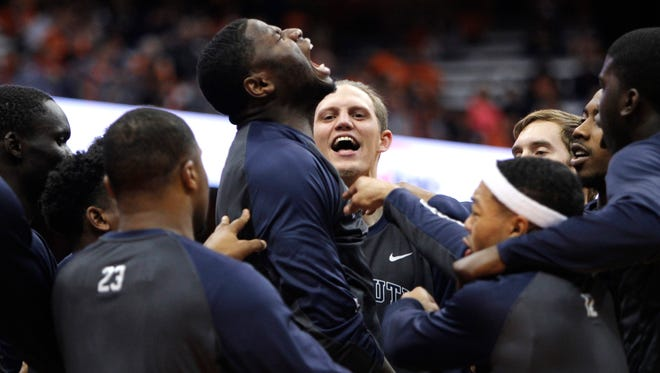 Monmouth's Sam Ibiezugbe, center, yells with teammates at the start of an NCAA college basketball game against Syracuse in Syracuse, N.Y., Friday, Nov. 18, 2016. (AP Photo/Nick Lisi)