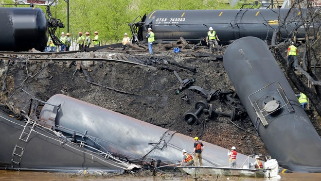 In this May 1, 2014, file photo survey crews in boats look over tanker cars as workers remove damaged tanker cars along the tracks where several CSX tanker cars carrying crude oil derailed and caught fire along the James River near downtown Lynchburg, Va.