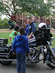 Burlington police Sgt. Paul Glynn lets kids from a Sara Holbrook Center after-school group sit on a police motorcycle and answers their questions during a community barbecue and open house at Battery Park on Thursday evening.