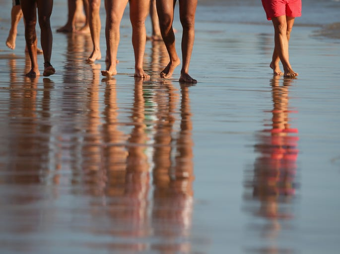 We may be freezing and buried beneath record snows this winter, but elsewhere in the world, it is warm. Competitors walk on the beach during the Australian Surf Rowers League Open Championships at Stockton beach on February 8, 2014 in Newcastle, Australia.