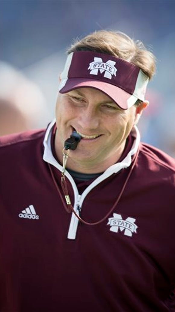 Mississippi State head coach Dan Mullen watches his team warm up before an NCAA college football game against Kentucky at Commonwealth Stadium in Lexington, Ky., Saturday, Oct. 25, 2014. (AP Photo/David Stephenson)