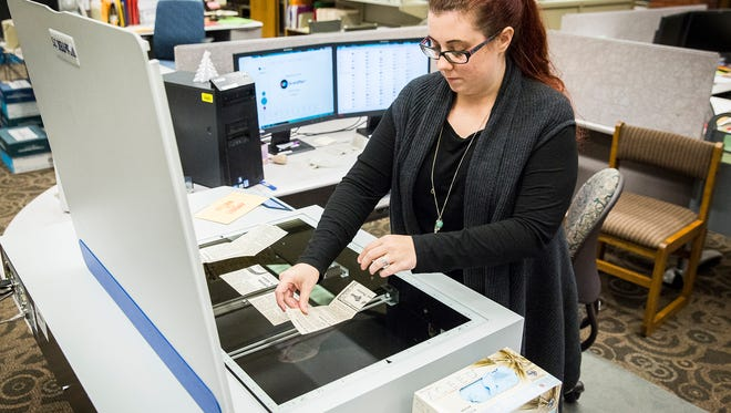 """Lauren Mayo, metadata and digital initiatives assistant at Bracken Library, scans old newspaper clippings from The Star Press as the school embarks on a project to digitize the newspaper's huge """"morgue."""""""