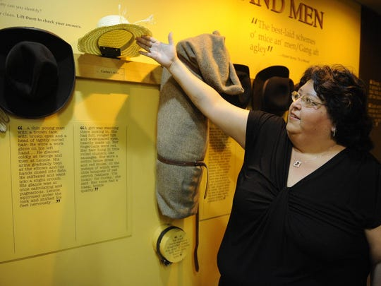 "Diane Arellano, volunteer coordinator, shows how the National Steinbeck Center is a hands-on museum as she lifts a hat in the ""Of Mice and Men"" exhibit at the museum."