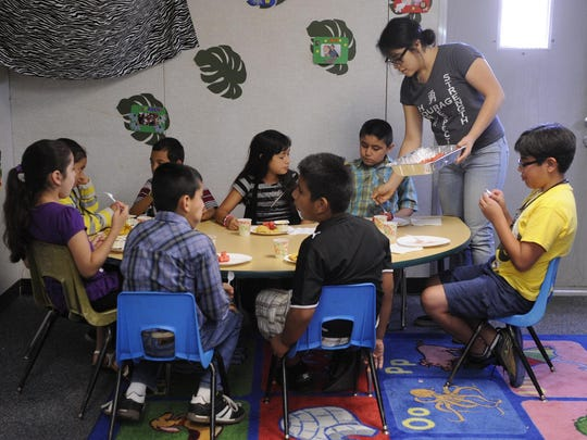 Daisy Cruz, 18, of Tulare, serves watermelon to children in grades 3-5 during lunch as part of the summer program at the Goshen Family Center. The center is run by Family Services of Tulare County and this program was sponsored by Western Milling.