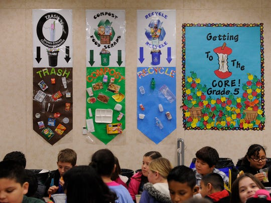 Color-coded posters made by student leaders detail what waste goes into trash, compost and recycle containers after lunch at Manuel Hernandez Elementary School. Since December, students have been separating their waste and cutting down on what goes into the landfill.