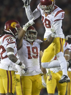 Southern California Trojans linebacker Michael Hutchings (19) is congratulated by defensive back Leon McQuay III (22), and linebacker Quinton Powell (18) after he brings down Penn State Nittany Lions running back Saquon Barkley (26) during the second half of the 2017 Rose Bowl game at the Rose Bowl.