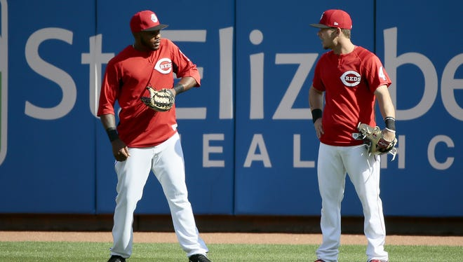 Cincinnati Reds prospect Phillip Ervin talks with Cincinnati Reds second baseman Scooter Gennett (4) in the outfield during batting practice before the MLB National League game between the Cincinnati Reds and the Chicago Cubs at Great American Ball Park in downtown Cincinnati, on Friday, April 21, 2017.
