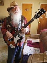 "Farmington resident Sherwood ""Woody"" Moore displays one of his bass guitars."