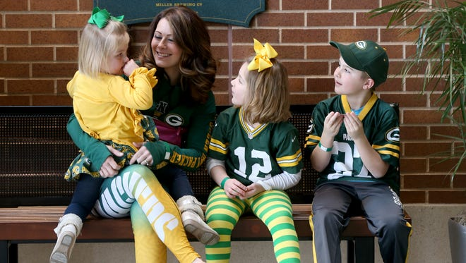 Amanda Furman, second left, of Appleton, waits with her children, all dressed in the Packers gear, for a stadium tour in the Lambeau Field atrium. Her children are, from left, Violet, age 3, Annah (CQ), age 6, and Drew, age 9.   - PACKFANS - Green Bay Packers fans and employees at Laumeau Field, as well as the city of Green Bay, suddenly finds itself preparing for a playoff game, on Monday, January 2, 2016  in what had looked to be a lost season. The Green Bay Packers will face the New York Giants in a wild-card playoff game on Sunday, January 8, 2017 at Lambeau Field. - Photo by Mike De Sisti / Milwaukee Journal Sentinel -