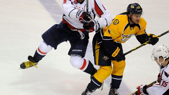 Capitals' Alex Ovechkin (8) and Predators' Roman Josi (59) battle for the puck during a game at Bridgestone Arena on Jan. 16, 2015.