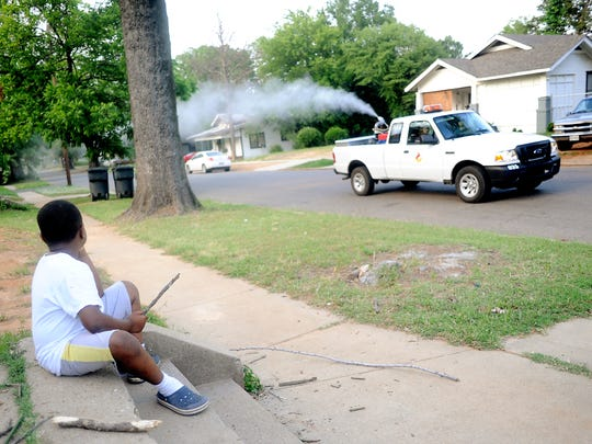FILE PHOTO - Javarrion Chism, 6, watches the mosquito control truck pass by his house in Shreveport's Queensborough neighborhood.